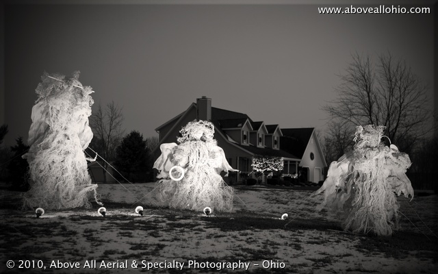 A trio of life-sized angels on display for Christmas in front of a home near Willard, Ohio; black and white conversion, vignette added
