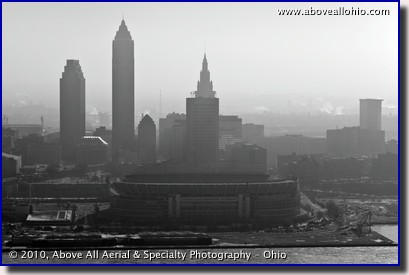 A low level aerial view of Cleveland Browns Stadium and downtown Cleveland on a hazy winter day.