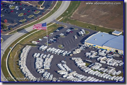 An aerial view of a huge flag waving above a local RV dealer.