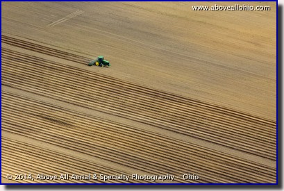 An aerial view of a farmer preparing a field for planting; near Greenwich, Ohio.