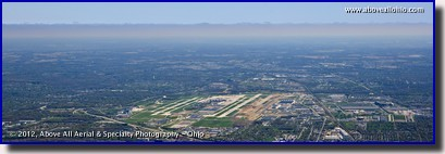 "A panoramic aerial view Port Columbus International Airport (""CMH"", Ohio) with a layer of solid overcast clouds in the distance."