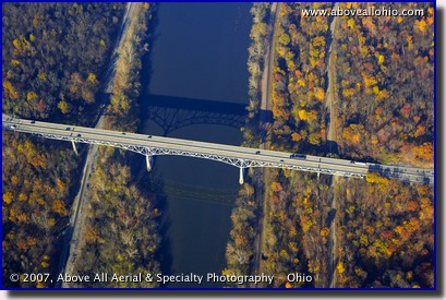 Aerial photograph of bridge over a river, train tracks, and fall trees