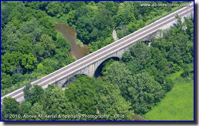 Aerial photograph of a stone arch railroad bridge