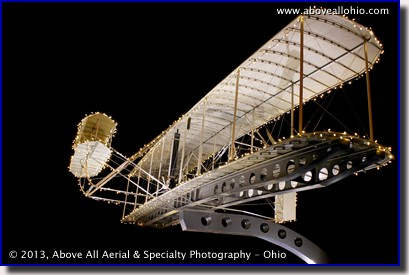 A ground-based night time architectural photo of the Wright Flyer replica at the Akron-Canton Regional Airport's Aviation Park.